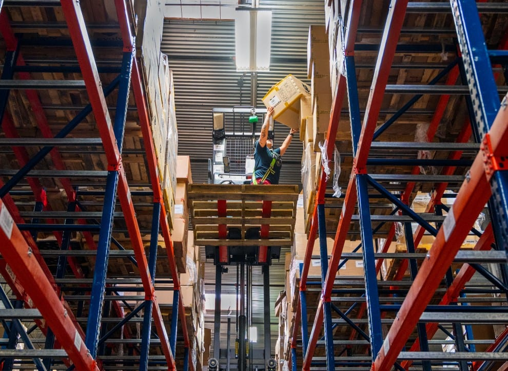KP Staffing Agency warehouse worker standing on pallet held by reach truck and stacking a box on red and blue shelving