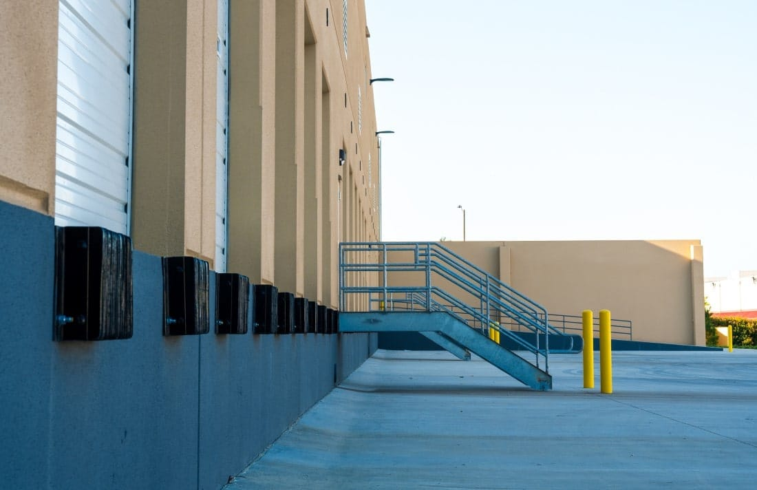 Warehouse docking station with stairs leading to door entrance.